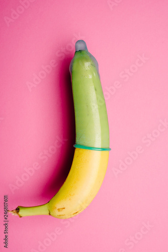 Foto op Canvas Akt Banana with green condom in front of pink background