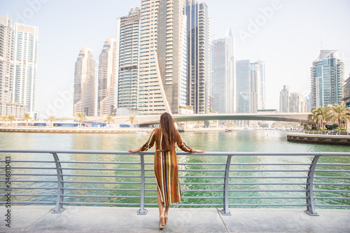 fototapeta na szkło Rear view of happy beautiful tourist woman in fashionable summer white dress enjoying in Dubai marina in United Arab Emirates. Luxury and comfortable tourism season in UAE.