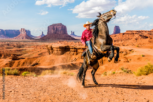 Obraz na plátne Cowboy Rearing Horse in Monument Valley