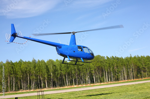 The aircraft - Blue small helicopter makes flight low height.
