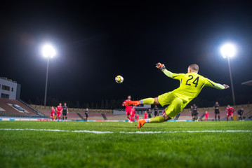 Goalkeeper in action, catching the ball, Football photo, Night Stadium