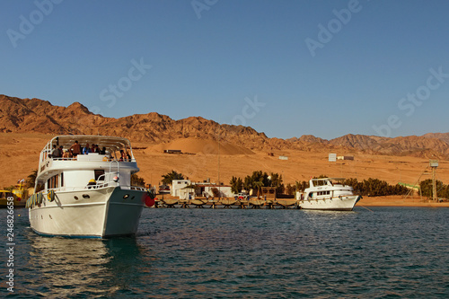 Dahab, Egypt ? JANUARY 06, 2019: Cruise ship with tourists goes to the reef where people will dive with scuba diving or snorkeling. Summer vacation and tourism concept