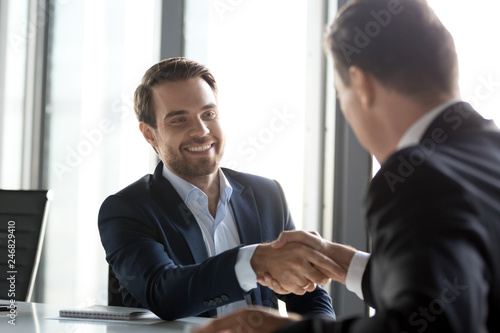 Happy businessmen in suits shaking hands after successful negotiations at meeting, male partners making business deal or good impression, thanking promising loyalty, respect gratitude handshake