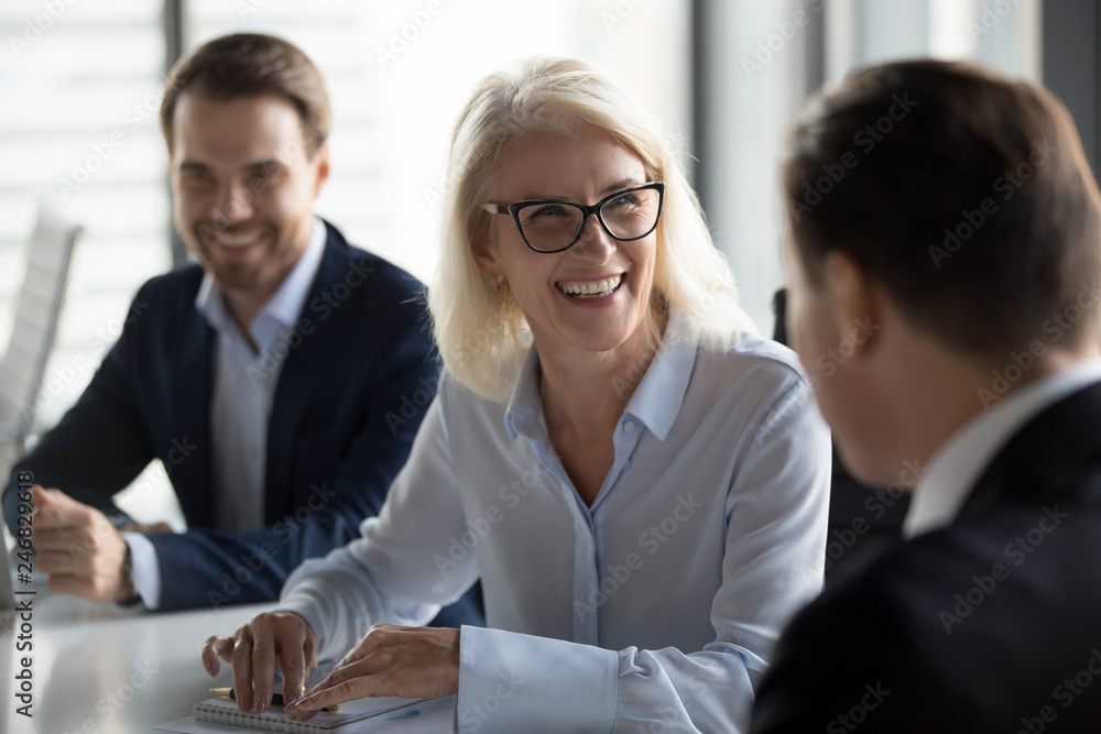 Fototapety, obrazy: Friendly middle aged female leader laughing at group business meeting, happy old businesswoman enjoying fun conversation with partner, smiling mature business coach executive talking to colleague