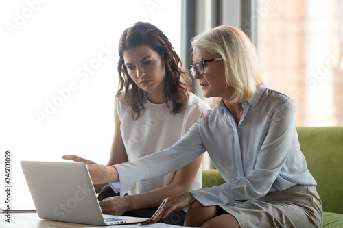 Canvas Print Serious middle aged executive manager explaining colleague online work together