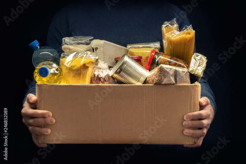 Photo sur Aluminium Magasin alimentation A man holding a donation box of different products on dark background