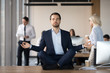 Leinwandbild Motiv Mindful calm businessman in suit meditating at office sitting in lotus position on work desk, successful ceo executive doing yoga exercise at workplace, peace of mind, no stress free relief concept