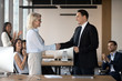 Executive ceo manager and middle aged female employee shake hands congratulating with promotion, rewarding praising motivating appreciating good result, respect feedback concept recognition handshake