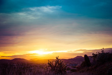 A Beautiful Image Of A Sunset Over A Desert With A Cactus In The Foreground And Mountains In The Distance.  The Sky Has Warm Golden Colors On The Horizon With Cool Blue Tones In The Clouds At The Top