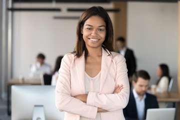 Smiling millennial african american corporate employee executive, mixed race office worker or team leader looking at camera, female young black professional business coach company manager portrait