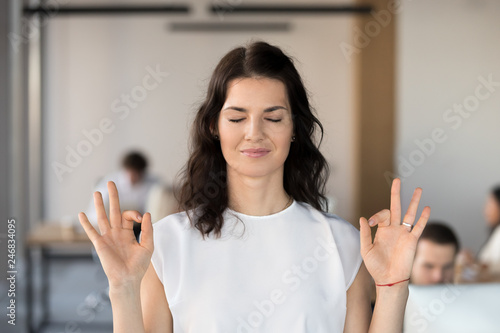 Young business woman employee meditating in office with eyes closed for no stres Canvas Print