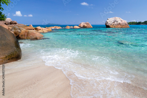 Foto op Plexiglas Strand Beach with blue water and blue sky and some rocks