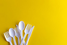 Minimalistic White Reusable Plastic Spoon Fork Knife Cutlery Isolated On Yellow Background Laying On The Table With Copy Space. Top View Flat Lay Perspective. Plastic Concern.