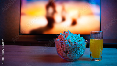 Fotografía  Popcorn in a glass plate with a drink on the background of the TV with the film on