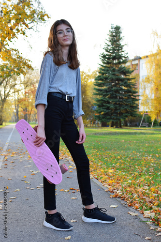 Fotografia  Pretty teen girl standing on sidewalk holding pink penny skate board wearing black jeans and sneakers smiling at camera on autumn tree landscape background