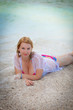 Young blonde woman in bikini and beach dress near at the beach in sea
