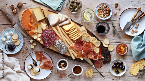 La pose en embrasure Entree Appetizers table with various of cheese, curred meat, sausage, olives and nuts Festive family or party snack concept. Overhead view.