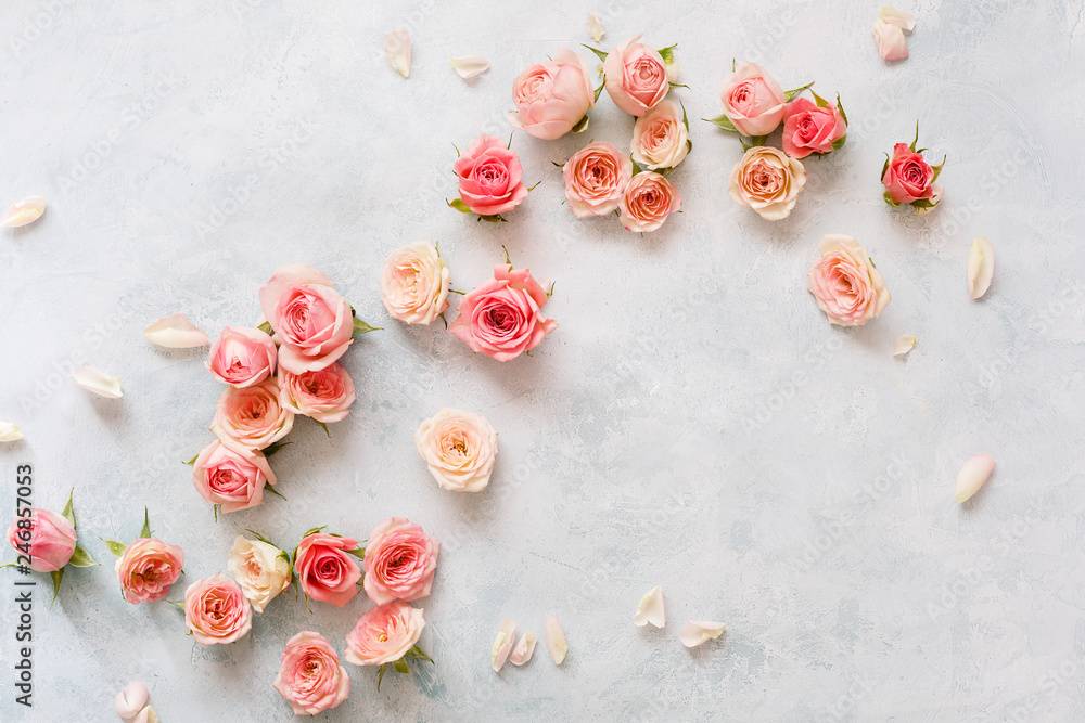 Fototapeta Roses On Textured Background. Various pink roses buds and petals  scattered on rustic background, overhead view, copy space