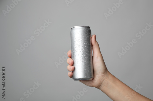 Fotografía Woman holding aluminum can with beverage on grey background, closeup