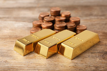 Shiny Gold Bars And Coins On Wooden Background