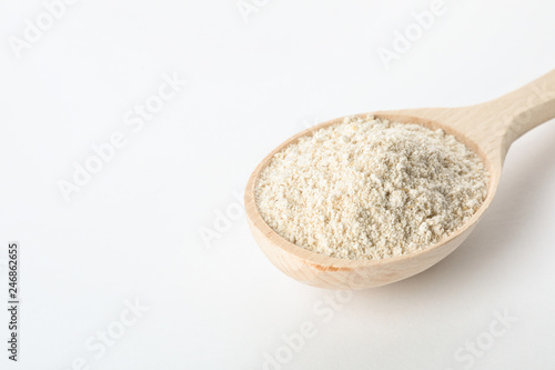 Spoon of oat flour isolated on white. Space for text