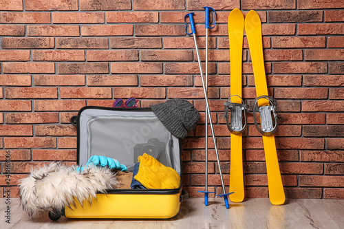Suitcase with clothes, camera and skis on floor against brick wall. Winter vacation