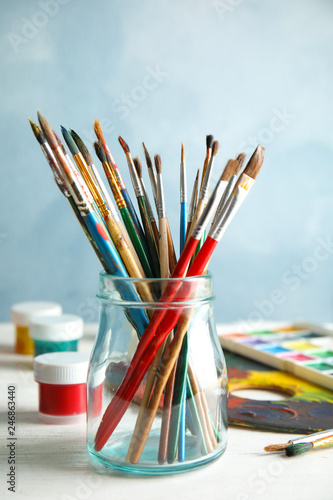 Glass jar with brushes and paints on table against color background