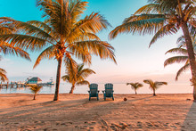 Two Empty Chairs At A Beach Su...