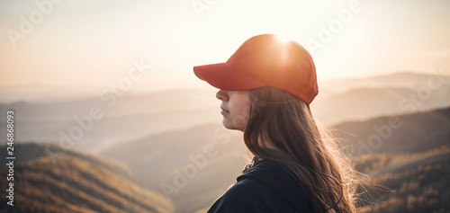 Valokuva  Girl with Red Baseball Cap in Beautiful Mountains