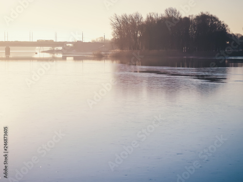 Photo Stands Lavender Frozen river with an island and a bridge in the background in winter