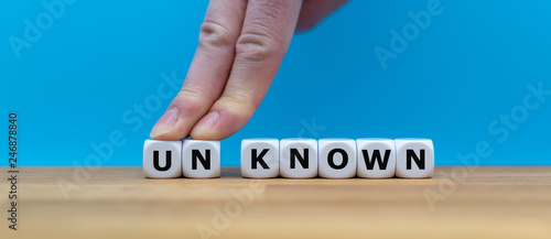 """Fotografia  Dice form the word """"UNKNOWN"""" while two fingers push the letters """"UN"""" away in order to change the word to """"KNOWN"""""""