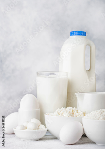 Fresh dairy products on white table background. Plastic bottle and glass of milk, bowl of cottage cheese and baking flour and mozzarella. Eggs and cheese.
