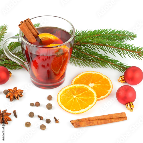 Hot red mulled wine isolated on white background with spices, orange slice, anise and cinnamon sticks.