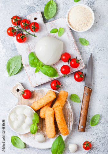 Fresh Mozzarella cheese on vintage chopping board with tomatoes and basil leaf and tray with cheese sticks on stone kitchen table background.