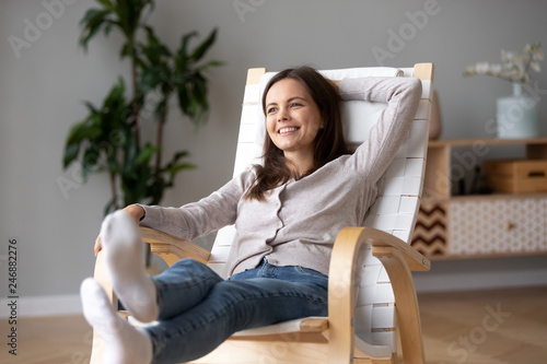 Happy calm young woman relaxing on comfortable wooden rocking chair in living room, smiling millennial girl having fun resting in armchair at home feeling stress free enjoying healthy weekend #246882276