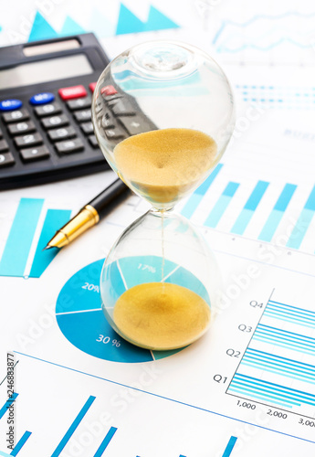 Hourglass on paper financial graphs. - 246883877