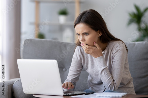 Vászonkép Shocked stressed young woman reading bad online news looking at broken laptop sc