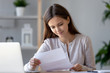 Smiling young woman doing paperwork holding letter of advice bill reading paper checking post mail at home, female customer receiving notification statement receipt from bank satisfied with good news