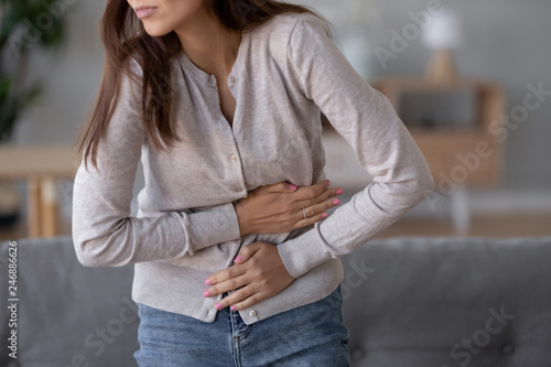 Valokuva  Stomachache concept, young sick woman standing holding belly suffering from stom