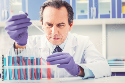 Fotografía  Ageing chemist placing test tubes in order