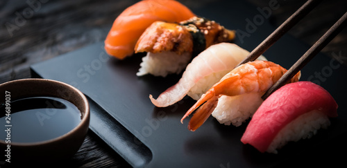 Photo Stands Sushi bar close up of sashimi sushi set with chopsticks and soy on black background