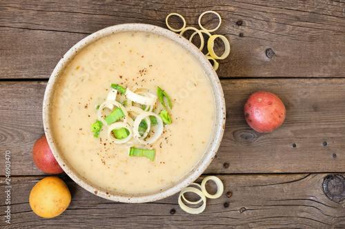 Obraz na płótnie Potato and leek soup. Top view on a rustic wood background.