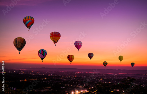 Poster Balloon The Colorful hot air Balloons flying above city on sunset time before dark coming with colorful of light and a beautiful twilight and sunset sky background.