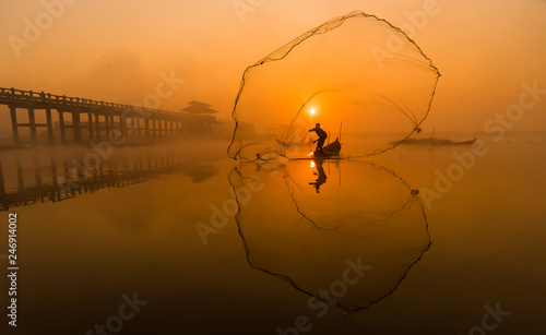 Photo Silhouette Asian fisherman on wooden boat casting a net for freshwater fish at U