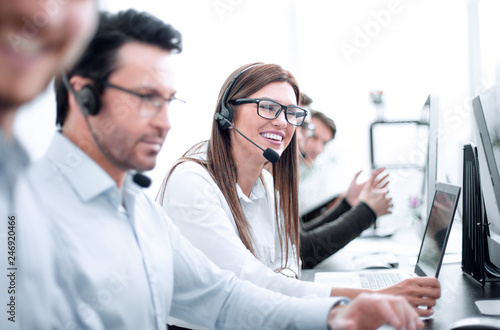 Fotomural woman call center operator and colleagues sitting at the Desk