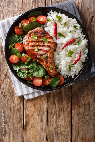 Grilled pork steak with rice garnish and fresh vegetable salad close-up. Vertical top view