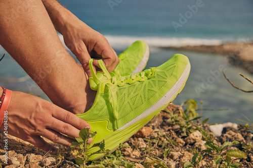 Fotografía  Sportsman tying jogging running sneakers above the ocean beach on a cliff