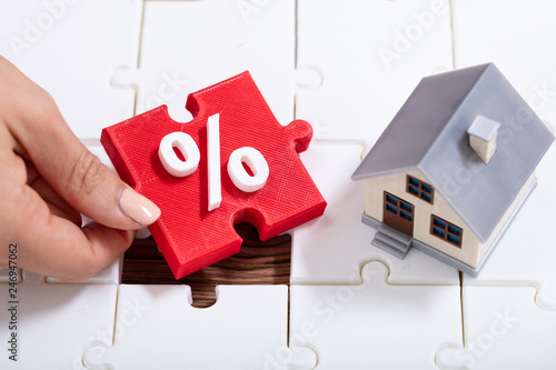 Person Holding Percentage Puzzle Pieces Near The House Model