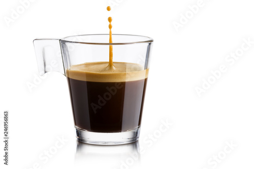 Czarna kawa w szklanej filiżance z doskakiwanie kroplą na białym tle