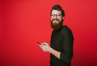 Leinwanddruck Bild - Happy bearded man in glasses typing sms adn looking at camera on red background